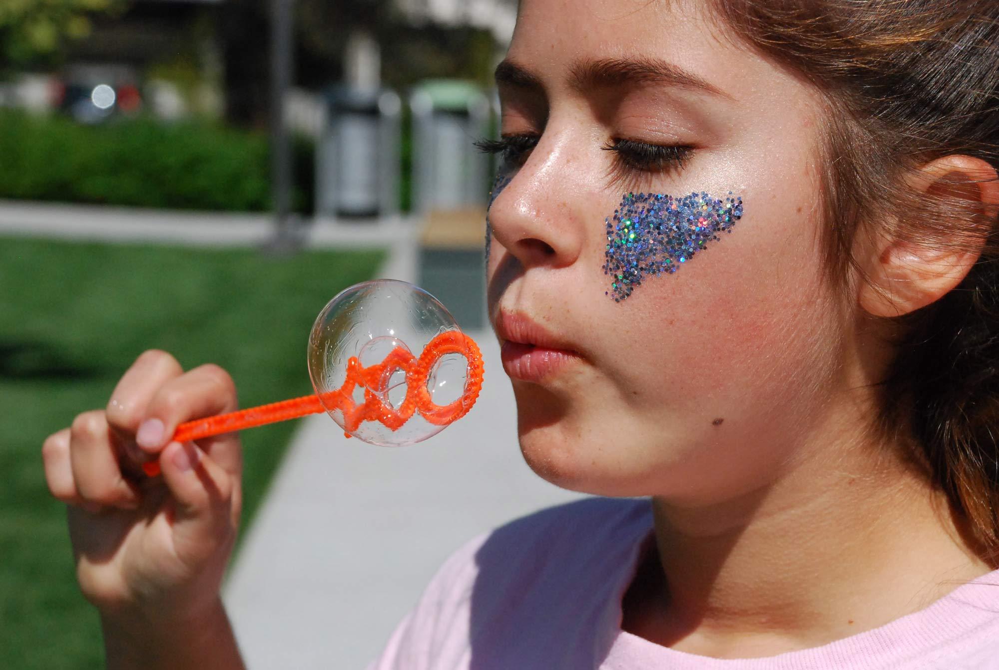 Niña soplando un juguete de hacer burbujas