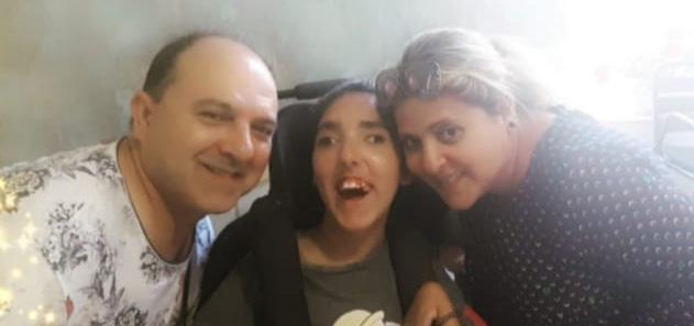 Carla, con parálisis cerebral infantil, junto a su madre y su padre